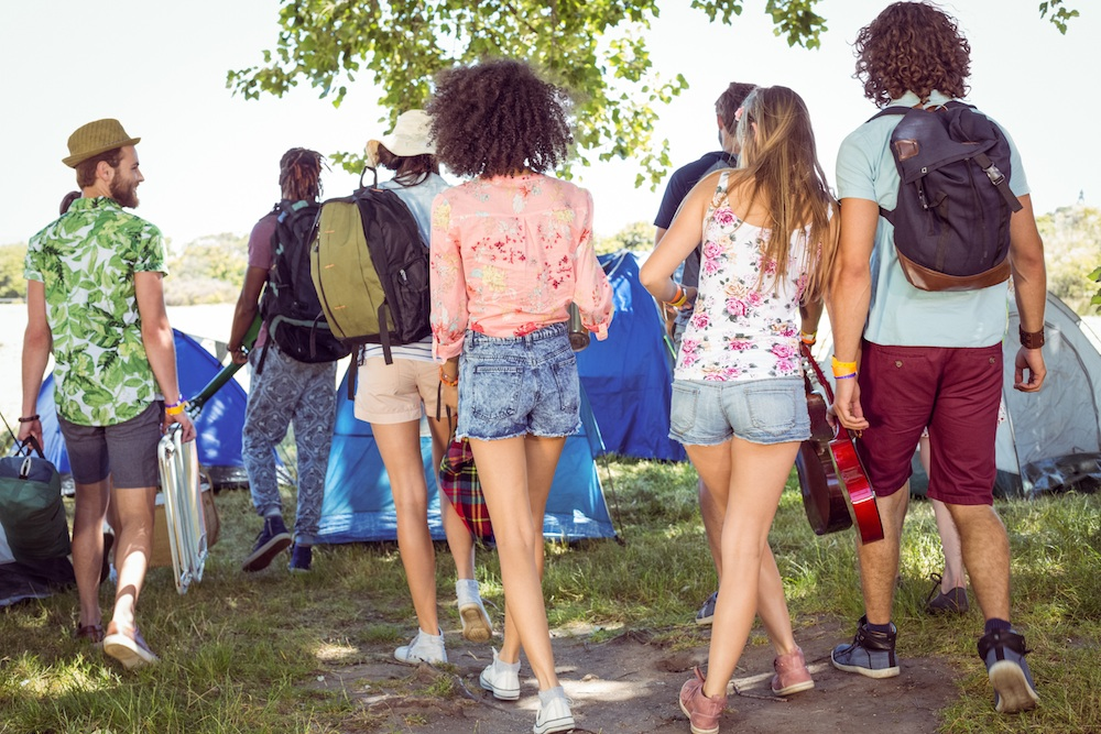 Young friends arriving at their campsite at a music festival