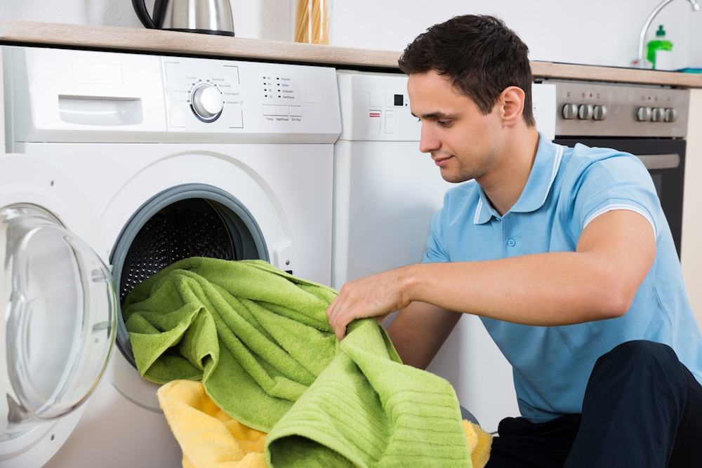 Student loading towels in washing machine